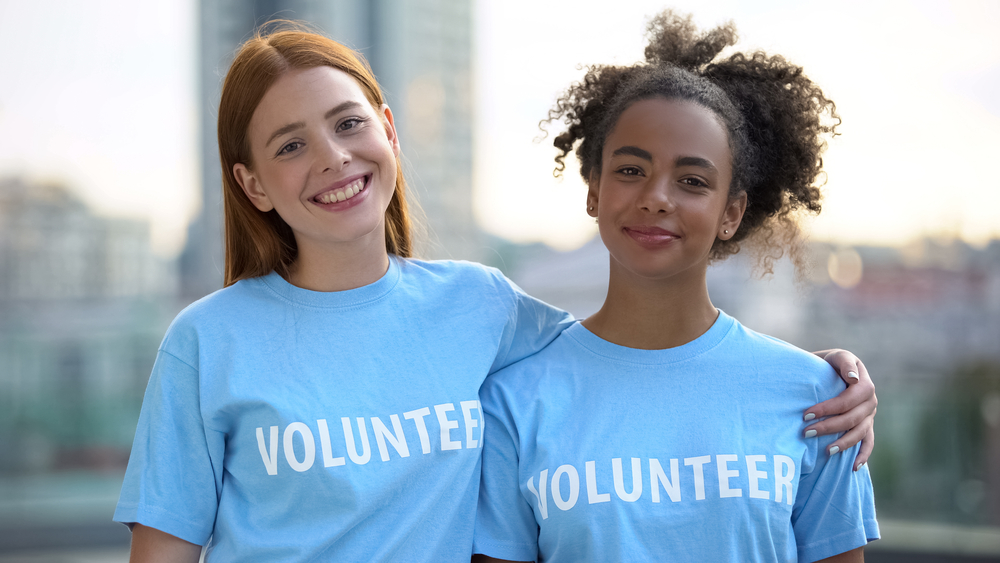 Two female volunteers smiling arm in arm to demonstrate  event volunteer sign up ease